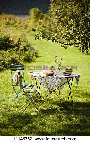 Stock Photo of A Table Set Outside in the Country with a Peach.
