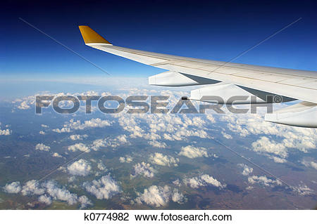 Stock Photo of Airplane wing over clouded globe k0774982.