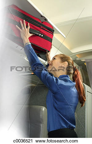 Stock Photography of A woman struggles to put her suitcase into.