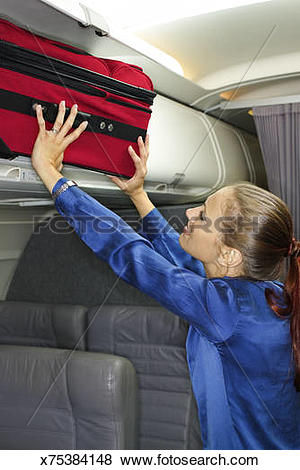 Pictures of Woman putting suitcase in overhead compartment.