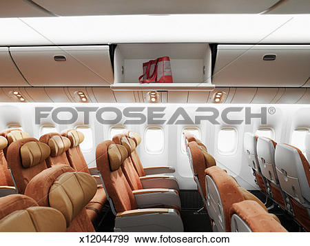 Stock Photograph of Empty airplane interior, bag left in overhead.