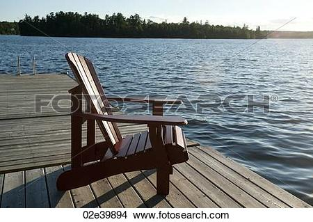 Stock Photo of Muskoka chair on the dock overlooking the lake at.