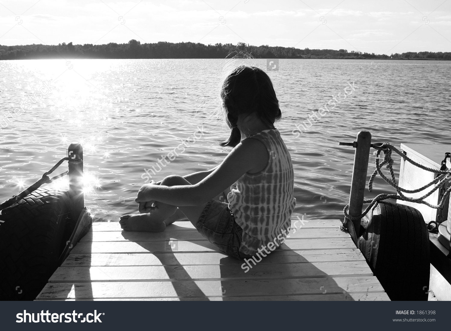 Black And White Image Of A Girl Sitting On A Pier, Overlooking A.