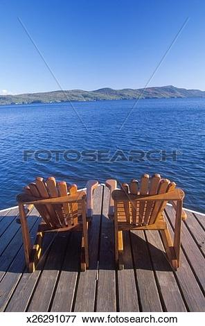 Picture of 'Two Adirondack chairs on a deck overlooking Lake.