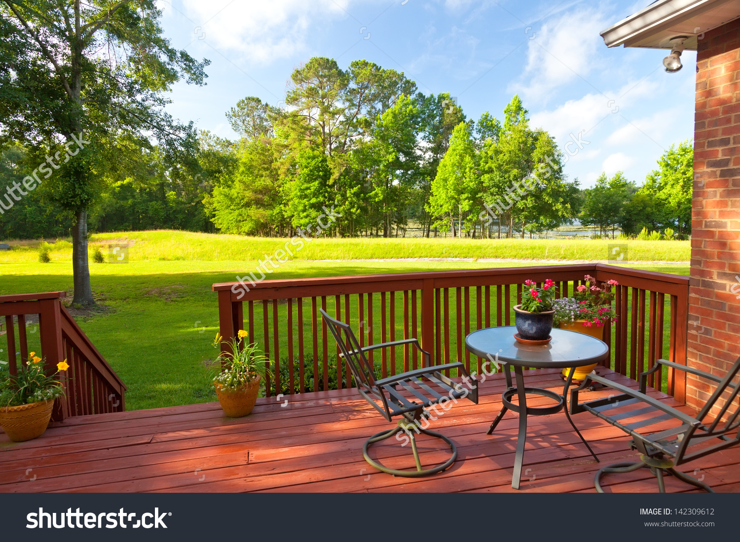 Residential Backyard Deck Overlooking Lawn Lake Stock Photo.