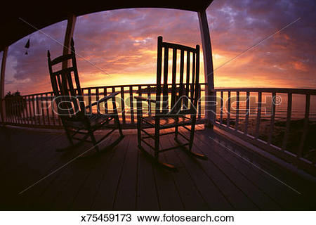 Stock Photo of Silhouette of rocking chairs sitting on a porch.