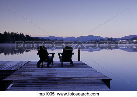 Stock Image of Two empty deck chair sit on dock at sunrise by.