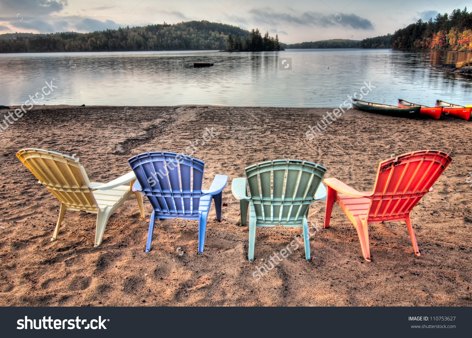 Four Colorful Patio Chairs Overlooking A Lake With Canoes Along.