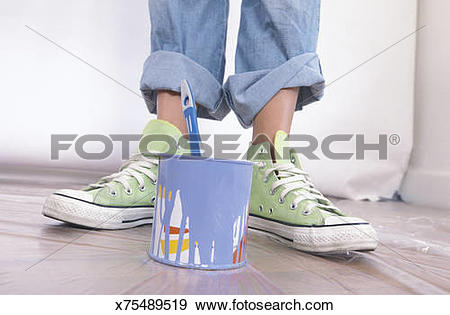 Stock Photograph of Person in tennis shoes with paint can.