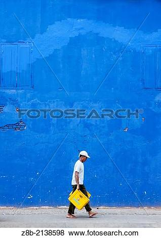 Pictures of Man In Front Of A Blue Wall, Pakse, Laos. z8b.