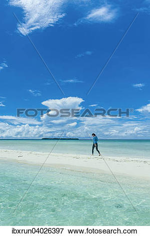 "Picture of ""Tourist walking on a sand strip at low tide, Rock."