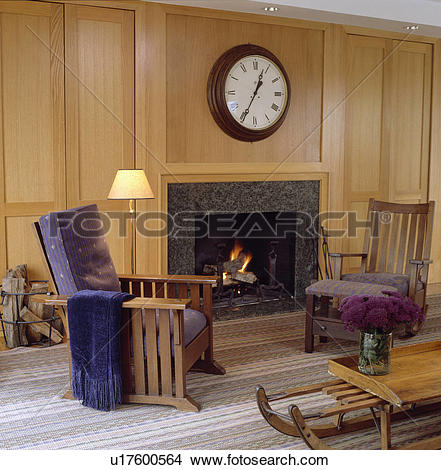 Stock Photo of Large circular clock above fireplace in panelled.