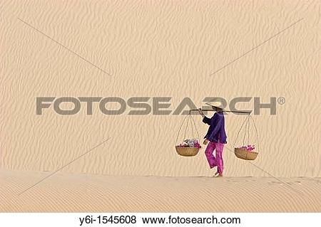 Pictures of Woman with conical hat carries flowers in pannier.