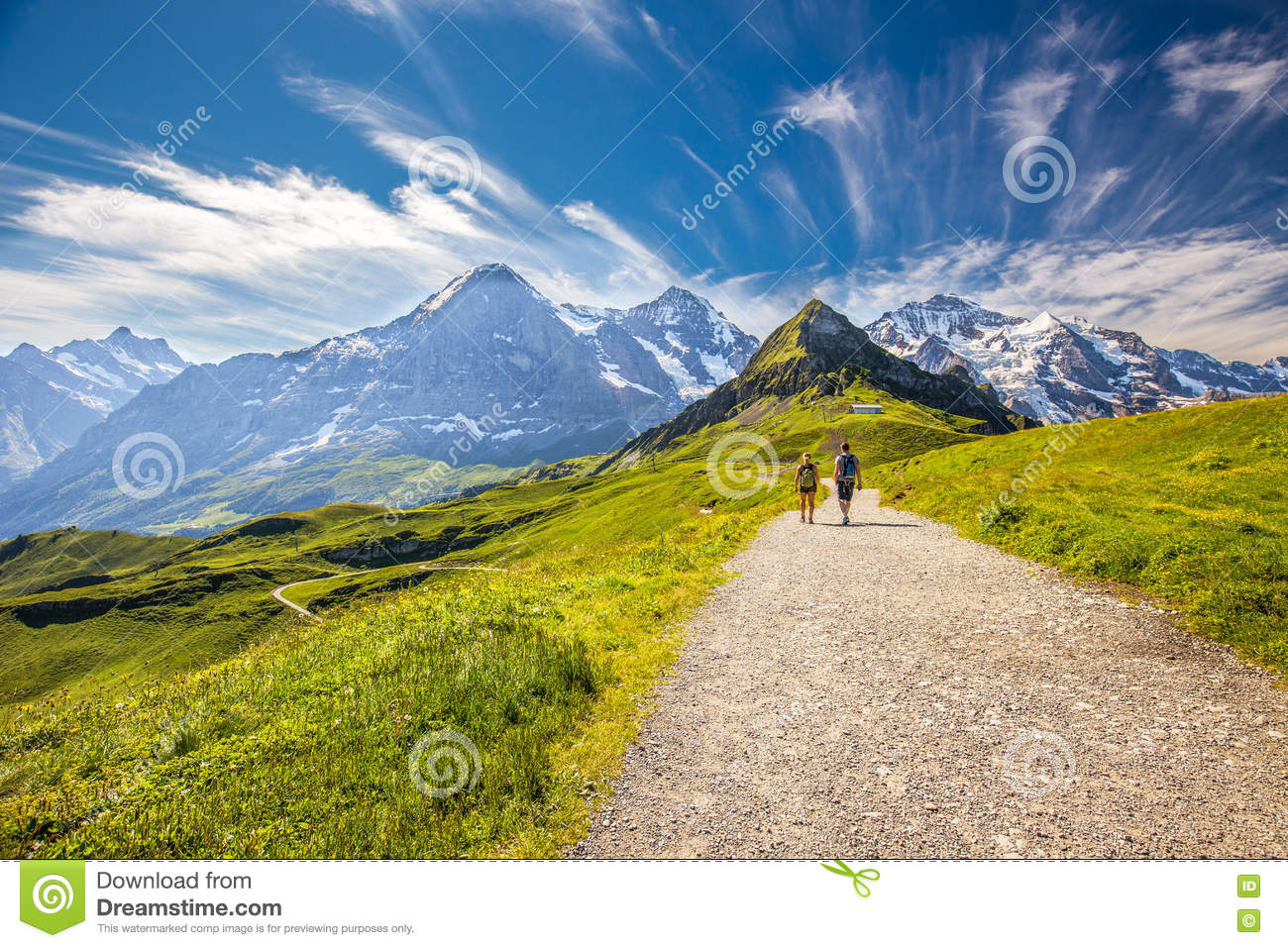 Young Couple Hiking In Panorama Trail Leading To Kleine Scheideg.