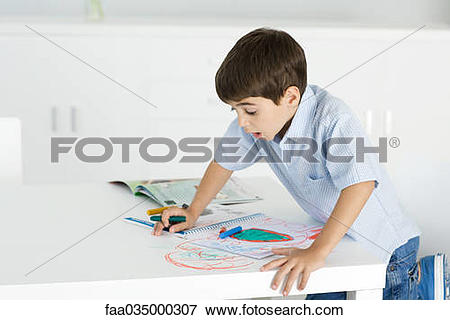 Picture of Boy leaning on table, holding crayon, colorful drawing.