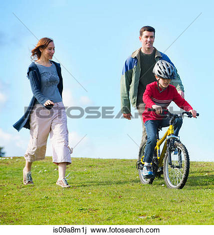 Stock Photo of Parents watching son riding bicycle is09a8m1j.