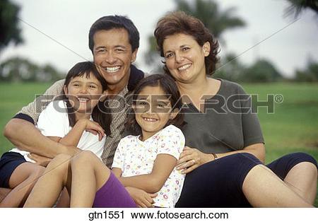 Stock Photography of Portrait of a happy hispanic family sitting.