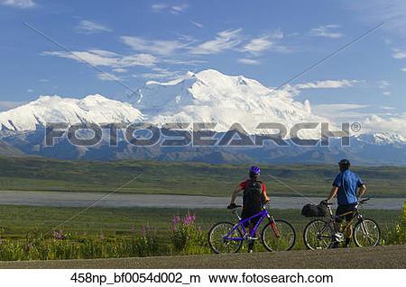 Stock Photo of Couple mountain biking on park road w/Mt McKinley.
