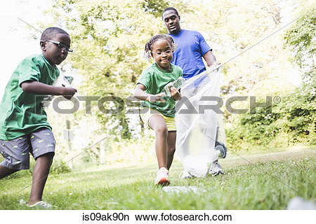 Stock Photo of Father picking up litter with son and daughter at.