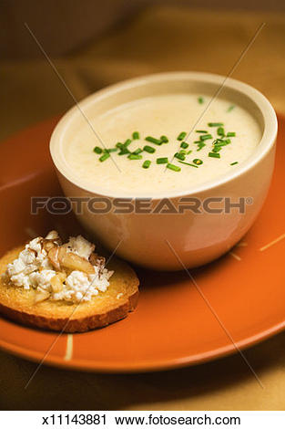 Stock Photography of Bowl of parsnip soup and crostini with cheese.
