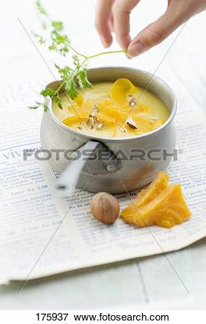 Picture of Parsnip soup with mimolette and crushed hazelnuts.