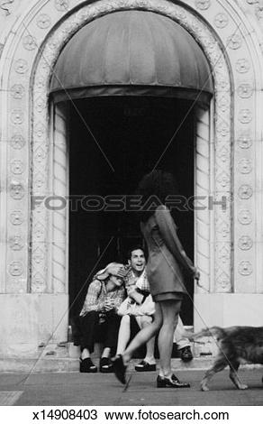 Stock Photo of Women sitting on steps watching passers by (B&W.
