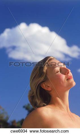 Stock Photo of Swedish woman sunbathing under passing cloud and.