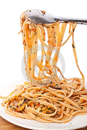 Spaghetti Lifted On The Pan With Tongs Stock Photo.