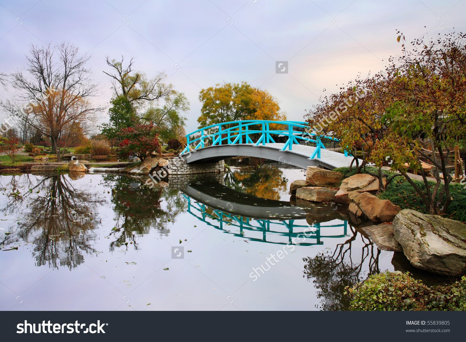 A Pastoral Scene Of A Japanese Foot Bridge Over A Quiet Little.