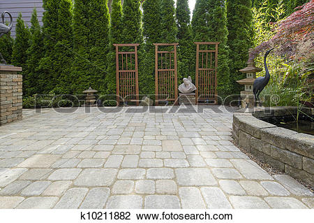 Stock Photo of Backyard Paver Patio with Pond and Garden.