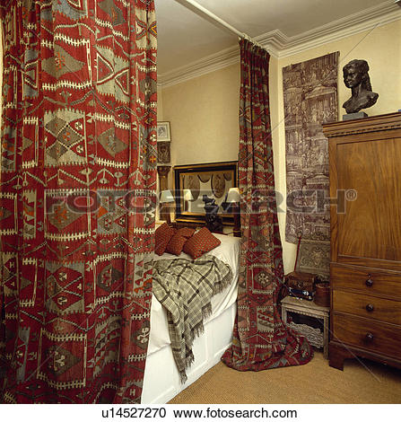 Stock Photography of Red patterned kelim rugs on curtain rail.