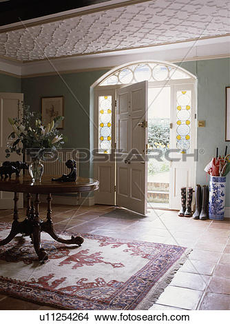 Stock Photo of Antique oval table and patterned rug in centre of.
