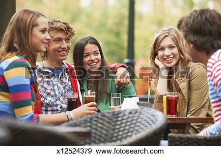 Stock Photograph of Young friends sitting in pavement cafe.