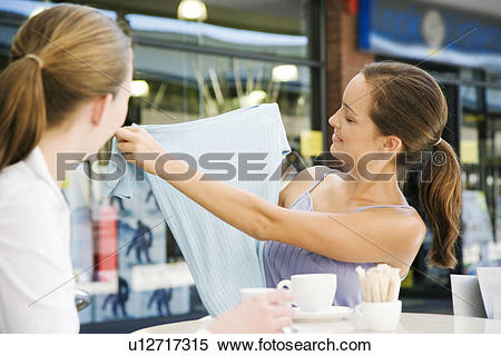 Stock Image of Woman showing clothes purchase to her friend over.