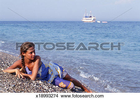 Stock Photo of Young woman wearing sarong, lying down on pebble.