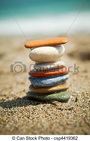 Stock Photo of Colorful stone stacks on a pebble beach.
