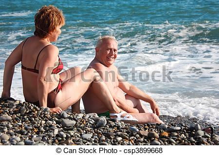 Pictures of aged pair sit on pebble beach, focus on man csp3899668.
