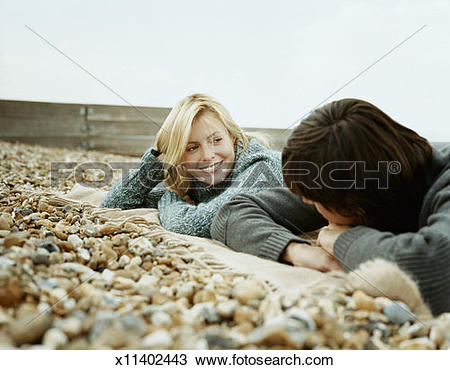 Stock Photo of Woman Gazing at a Man as they Lay on a Rug, on a.