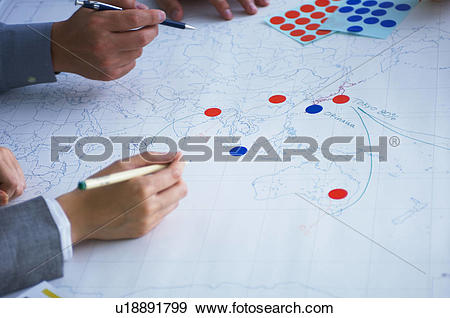 Stock Photograph of Business people making plans with map.