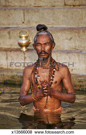 Pictures of Sadhu (holy man) performing rituals in river x13566008.