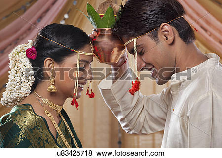 Pictures of Smiling Maharashtrian couple performing rituals before.