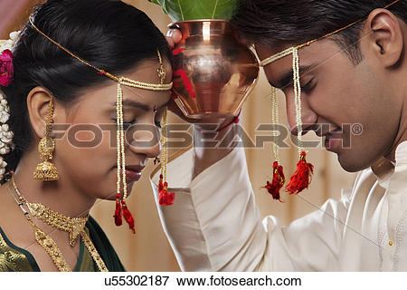 Picture of Young Maharashtrian bride and groom performing rituals.