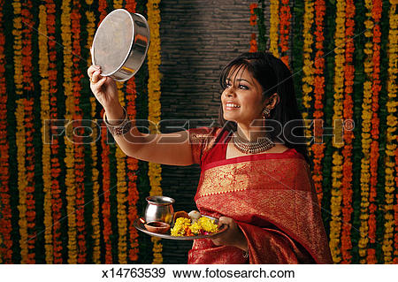 Stock Photograph of Woman performing a ritual of Karva chauth.