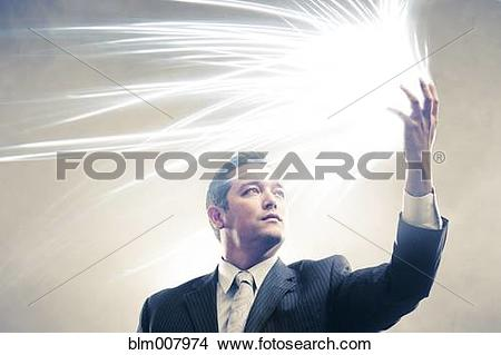 Stock Photo of Light radiating from Japanese businessman's hands.