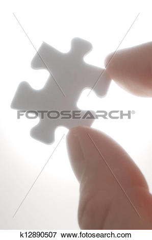 Picture of A person picking up one puzzle pieces against the light.