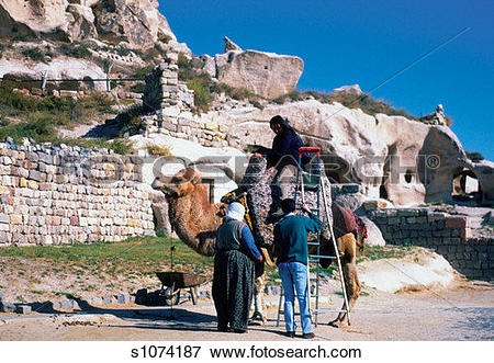 Picture of Person sitting on a camel with two people standing.