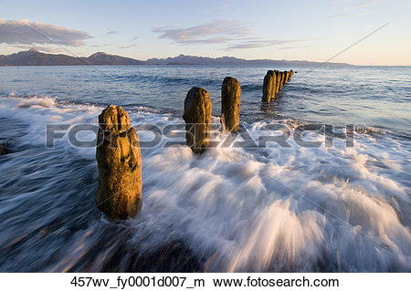 Stock Photo of Surf rushing around old pilings along beach Homer.