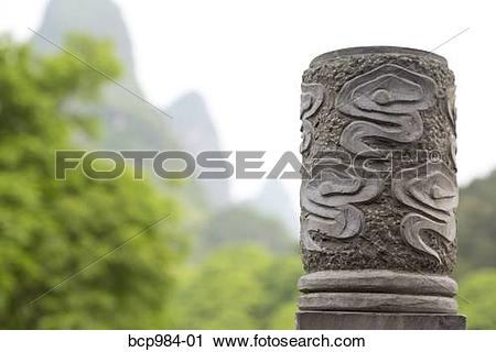 "Stock Photography of ""Karst mountains behind a carved stone pillar."