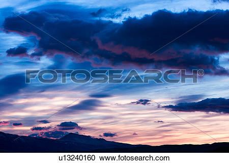 Stock Photography of Sunrise with dramatic blue grey clouds, pink.