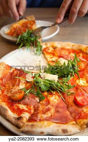 Stock Photo of Man Taking Slice of San Daniele Pizza with Rucola.
